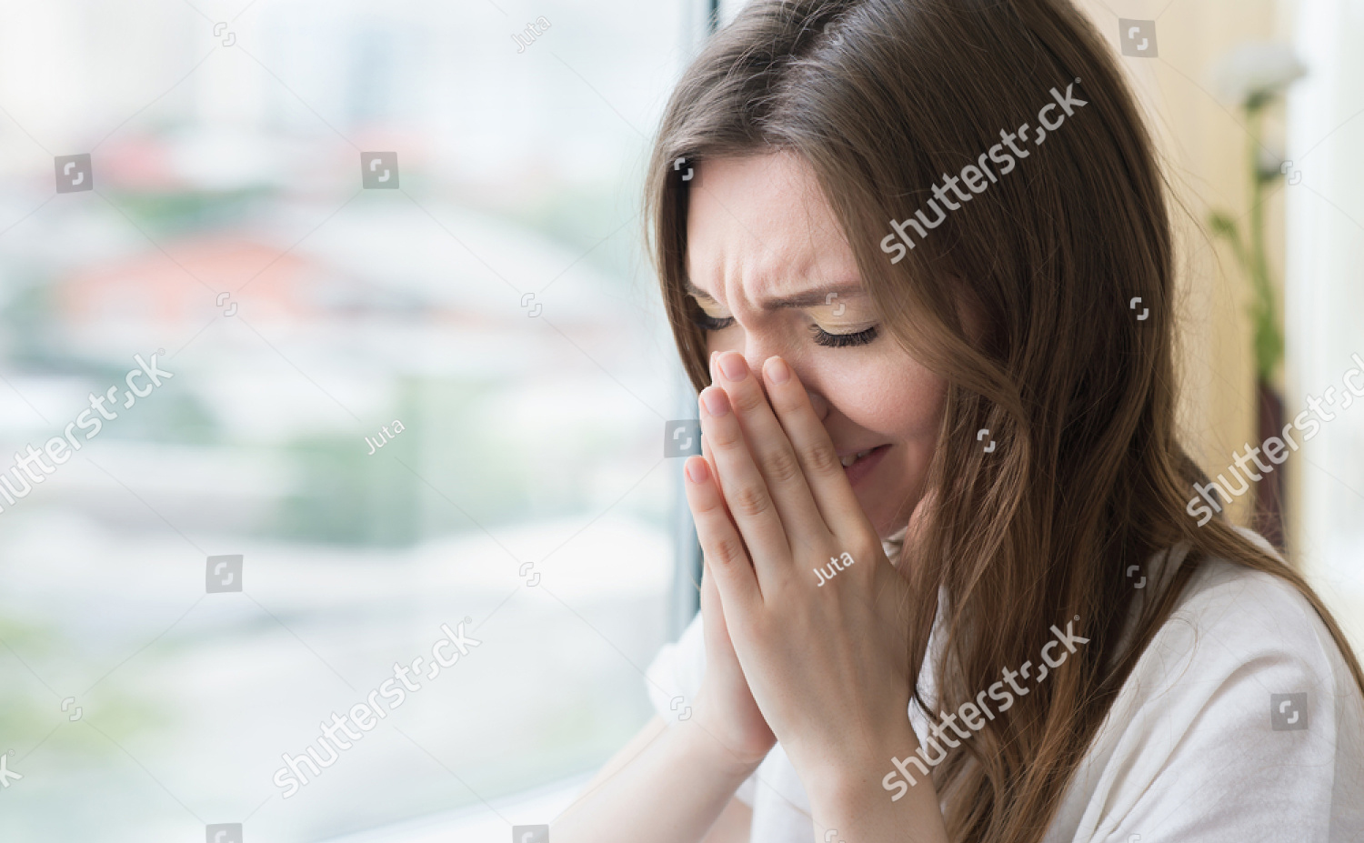 Stock photo young sad woman sits alone front of the window crying girl allergy illness depression stress 451347517